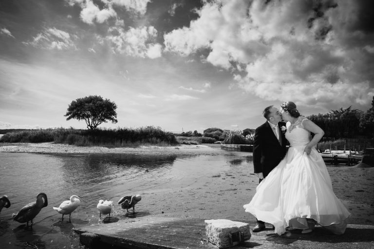Pam & Jon couple portrait by the water at Christchurch Harbour Hotel and Spa. Taken by Chris Jones of Lucy Boynton Photography.